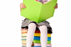 Little girl sitting on stack of books.
