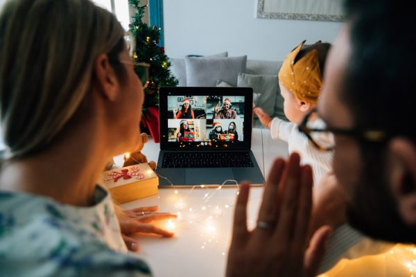 Family celebrating Christmas with their relatives respecting social distancing. They are doing a video call using a laptop to celebrate together. New normal during Coronavirus Covid-19 pandemic concept.