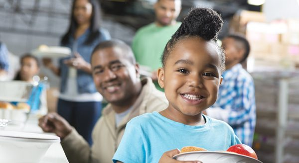 Preschool age African American child at soup kitchen with family