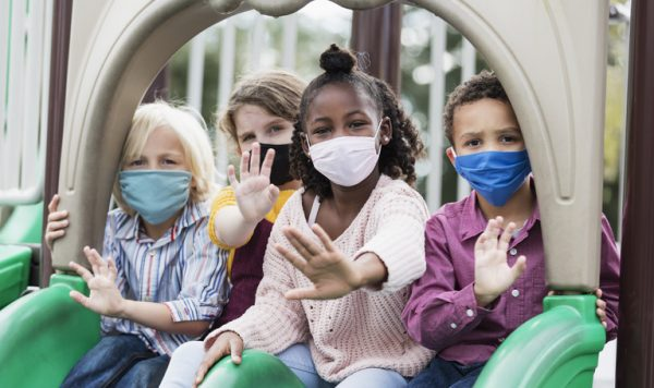 A multi-ethnic group of four children, 5 to 7 years old, playing together on a playground during school recess. They are sitting side by side on two slides, looking at the camera, waving. They are all wearing masks, back to school during the COVID-19 pandemic, trying to prevent the spread of coronavirus.