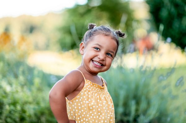 Portrait of a cute little cheerful mixed race girl in a yellow summer rummper.